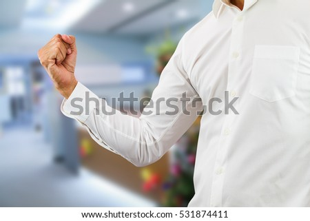 Business man wearing white shirt raising right fist up with cheerful on blurred office background