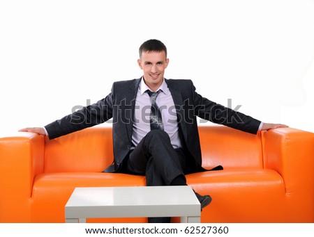 Business man who achieved success on an orange sofa - stock photo