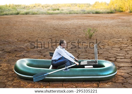 Business man will rows home for shore in paddle powered row boat in boat looking at  laptop rocks looks future symbol crisis losses braking difficulties environmental disaster water scarcity drought - stock photo