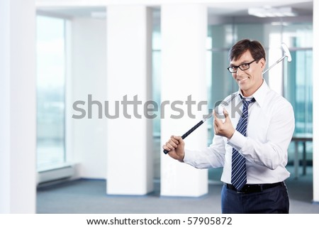 Business man with a golf club in office - stock photo