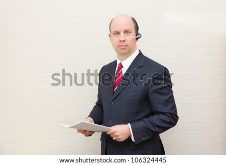 Business man with a handsfree telephone headset holding a document.