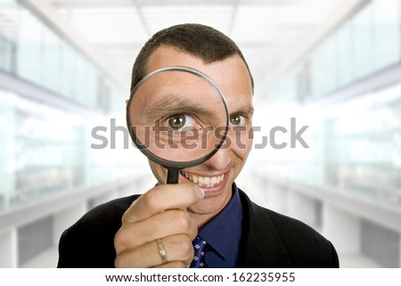 business man with a loupe at the office - stock photo