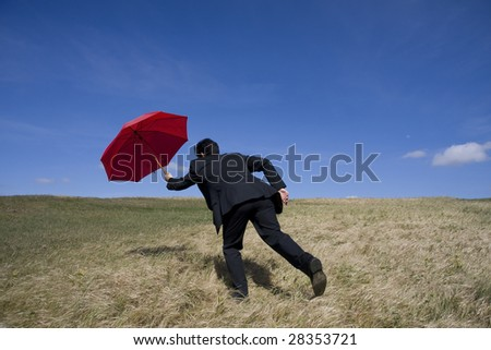 Business man with an open umbrella on the meadow - stock photo
