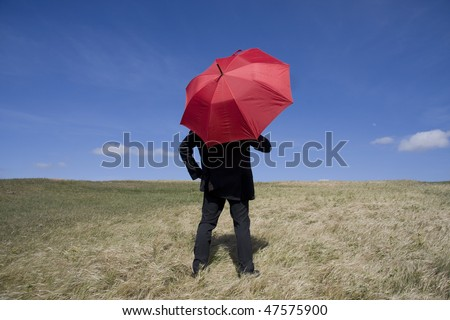 Business man with an umbrella on the meadow