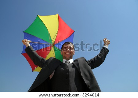 business man with arms wide open and colour umbrella - stock photo