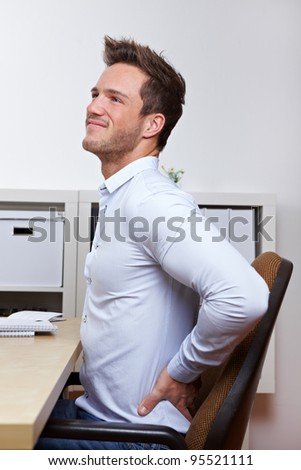 Business man with back pain in office chair at desk - stock photo