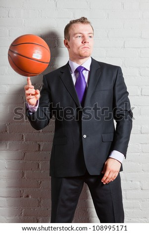 Business man with basketball. Good looking young man with short blond hair. Gym indoor. - stock photo