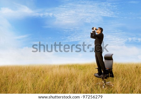 Business man with binoculars looking to the future