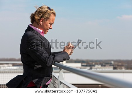 Business man with blue suit outdoor on rooftop using tablet.