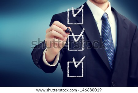 Business man with check boxes over navy blue background - stock photo