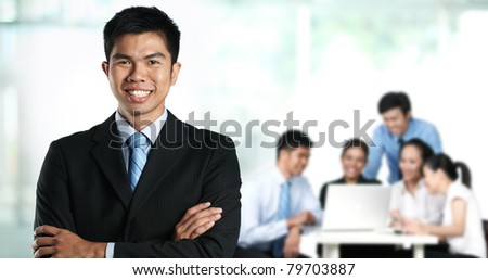 Business man with colleagues out of focus in background - stock photo