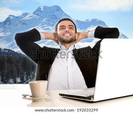 Business man with computer sitting at office desk thinking and dreaming of winter ski vacation and holidays in the Alps