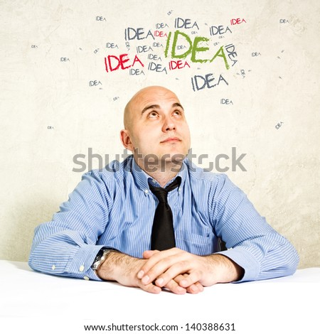 Business man with creative ideas buzzing around his head. Businessman looking up at ideas swarming around his head.