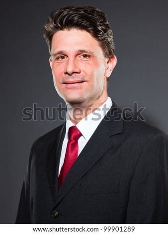 Business man with dark grey suit and red tie isolated on dark background. Studio portrait.