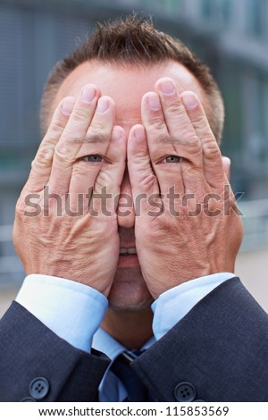 Business man with eyes on his hands over his face - stock photo