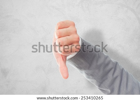 Business man with grey suit hand. With the thumb down. Over concrete wallpaper