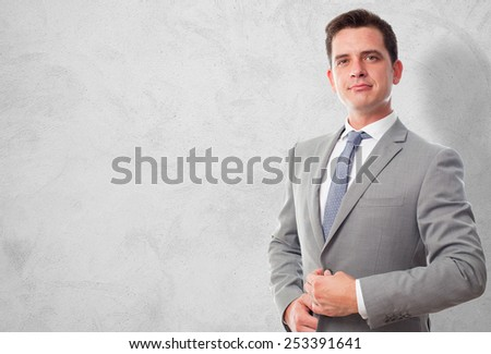 Business man with grey suit. He is looking confident. Over concrete wallpaper - stock photo