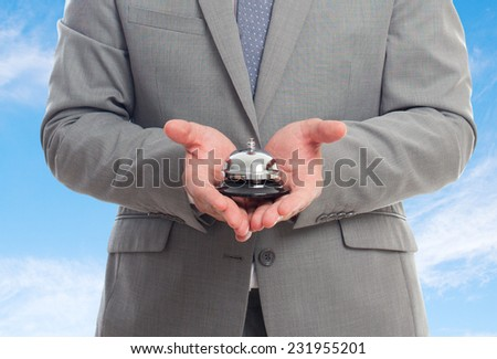 Business man with grey suit over clouds background. Holding a hotel bell - stock photo