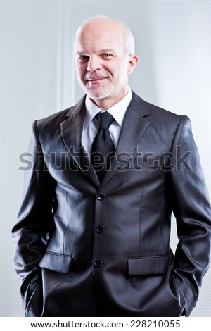 business man with hands in his pocket smiling with evident self confidence - stock photo