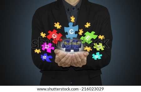 """Business man with  jigsaw puzzle piece  """"BUSINESS"""" and success - stock photo"""