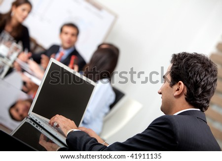 Business man with laptop in a meeting