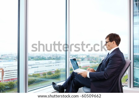 Business man with laptop in the office - stock photo