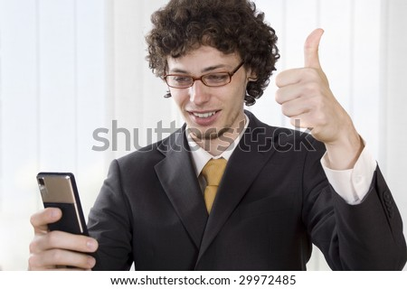 Business man with mobile phone giving a thumbs up