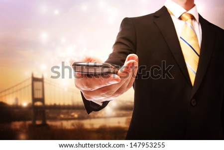 Business man with mobile phone on a bridge background - stock photo