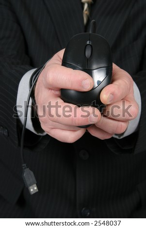 Business man with mouse cord wrapped around hands - stock photo