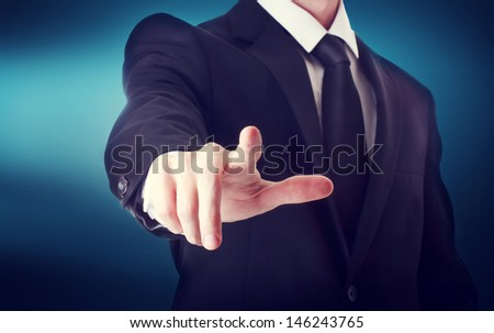 Business man with pointing to something or touching a touch screen on blue background - stock photo