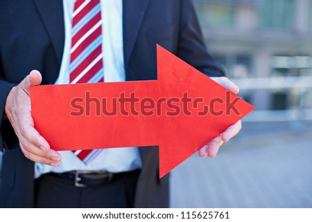 Business man with red arrow pointing to the right - stock photo