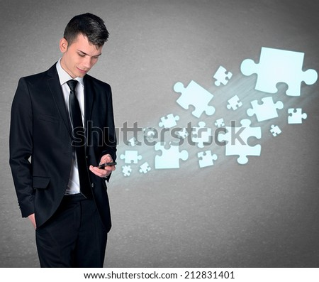 Business man with smartphone and puzzle - stock photo