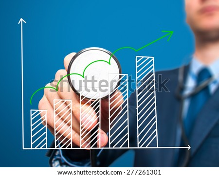 Business man with stethoscope examining graph, business analysis. Isolated on blue. Business, technology, health, finance concept. Stock Photo - stock photo