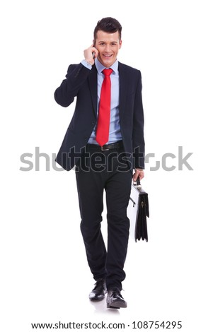 Business man with suitcase walking towards the camera while talking on the phone over white background - stock photo