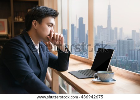 Business man with tablet computer at coffee shop - stock photo