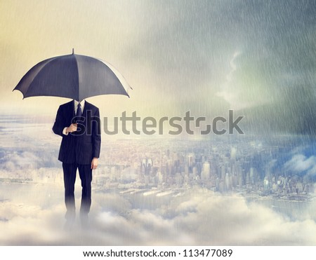Business Man with Umbrella Above the City - stock photo