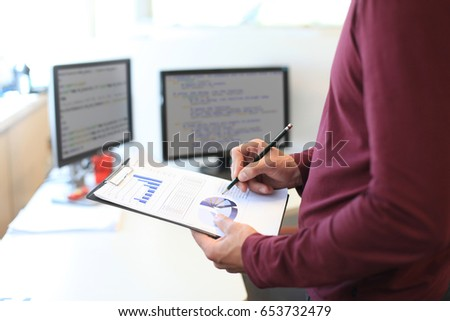 Business man working at office with graph data documents on his desk.