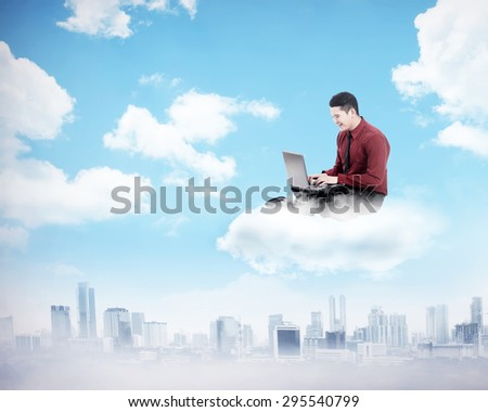 Business man working on the cloud above the city. Cloud computing concept - stock photo