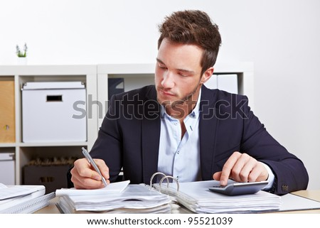 Business man working with calculator and files in office - stock photo