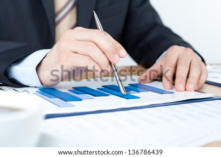 Business man working with diagrams. Close up of hands and documents