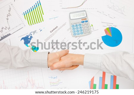 Business man working with financial data - shaking hands over contract - stock photo