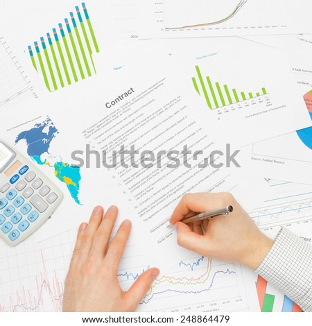Business man working with financial data - signing contract - studio shot - stock photo