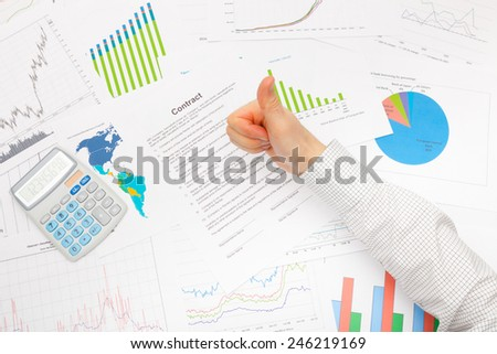 Business man working with financial data - thumb up - stock photo