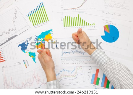 Business man working with financial data - thumbs up - focus on graphs - stock photo