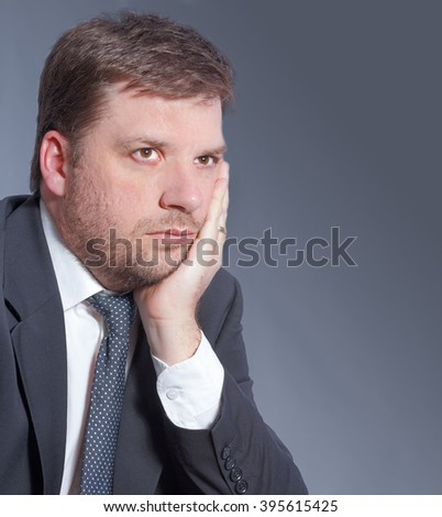 Business man worried about financial plan isolated on grey background