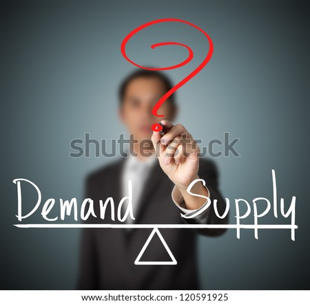business man writing demand and supply compare on balance bar - stock photo