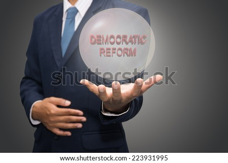 business man writing DEMOCRATIC REFORM concept  - stock photo