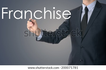 business man writing franchise concept on blue background - stock photo