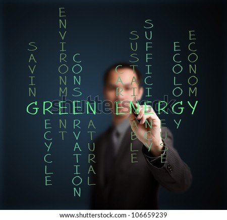 business man writing green energy concept by crossword - stock photo
