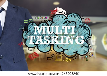 business man writing MULTITASKING over the cloud with office background , business concept , business idea - stock photo